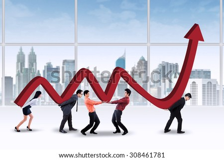 Portrait of young businesspeople carrying profit chart together in the office - stock photo
