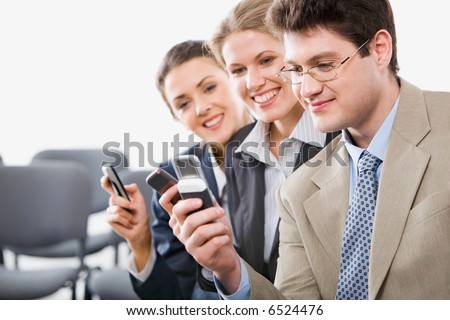 Portrait of young businesspeople sharing info on mobile phones in the room - stock photo