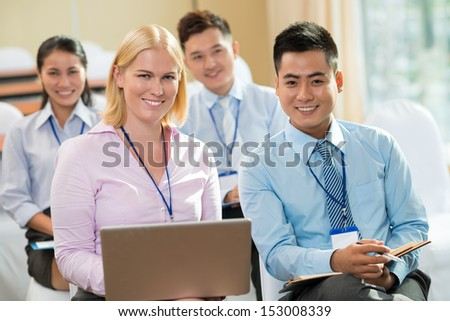 Portrait of young businesspeople with a laptop smiling and looking at camera in the foreground - stock photo