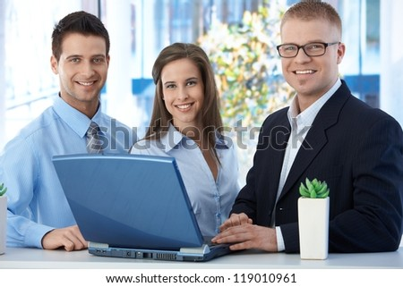 Portrait of young businessteam standing in office, using laptop computer, smiling at camera.