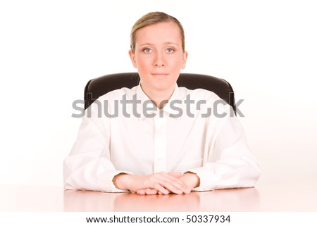 Portrait of young businesswoman at desk, white studio background.