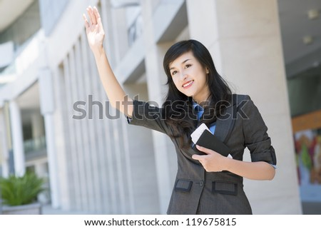 Portrait of young businesswoman catching taxi outside - stock photo