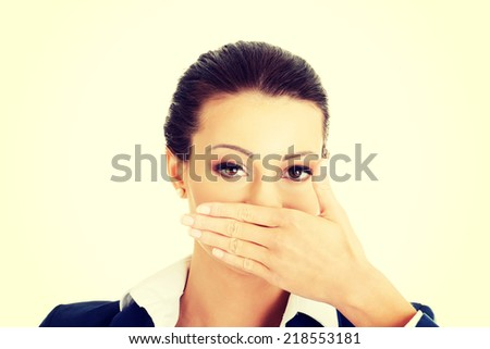 Portrait of young businesswoman covering with hand her mouth, isolated on white background - stock photo