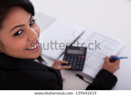 Portrait Of Young Businesswoman Doing Calculations In The Office - stock photo