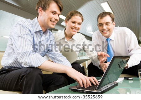 Portrait of young businesswoman holding documents and pointing at the monitor of laptop surrounded by two men