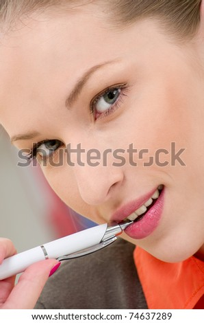 portrait of young businesswoman holding pen in mouth looking in camera - stock photo