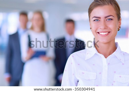 Portrait of young businesswoman in office with colleagues in the background - stock photo