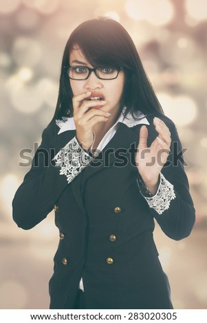Portrait of young businesswoman looks scared, shot with festive light background - stock photo