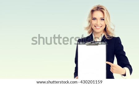 Portrait of young businesswoman showing blank clipboard, with copyspace area for text or slogan