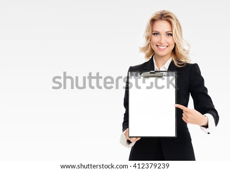 Portrait of young businesswoman showing blank clipboard, with copyspace area for text or slogan, on grey background, with blank copyspace area for text or slogan - stock photo