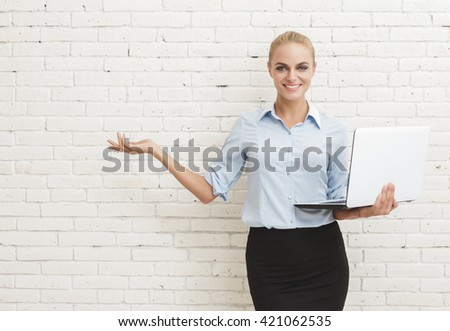 portrait of young businesswoman standing and holding laptop while presenting copy space at white brick wall background - stock photo