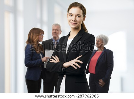 Portrait of young businesswoman standing at office with arms crossed while her colleagues consulting at background.  - stock photo