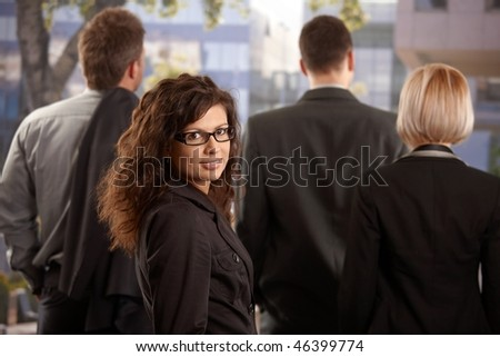 Portrait of young businesswoman standing outdoor, looking back, smiling. - stock photo