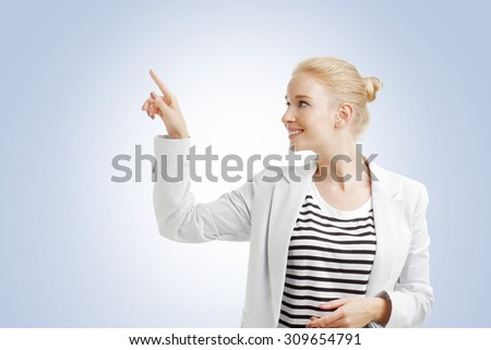 Portrait of young businesswoman standing showing something by her index finger.