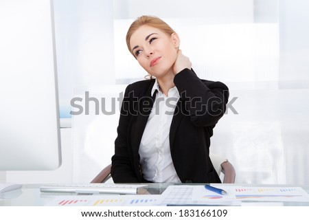 Portrait Of Young Businesswoman Suffering From Neck Pain - stock photo