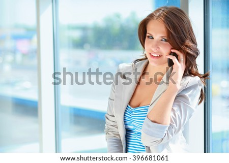 Portrait of young businesswoman talking on mobile phone on office hallway. - stock photo