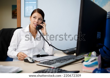 Portrait of young businesswoman talking on phone in office - stock photo