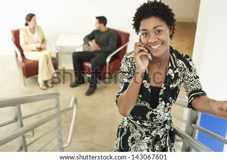 Portrait of young businesswoman using mobile phone on stairway with colleagues discussing in background - stock photo