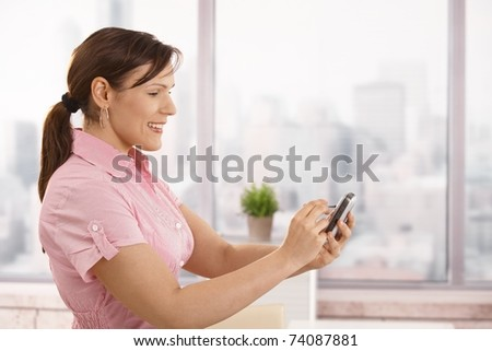 Portrait of young businesswoman using smartphone in office, smiling.? - stock photo