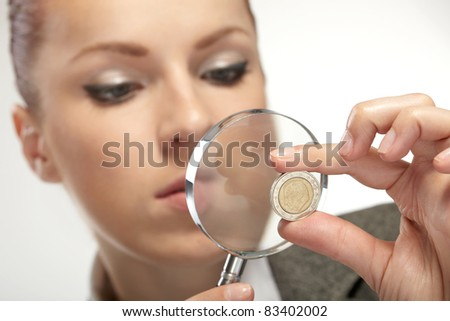 portrait of young businesswoman with magnifying glass - stock photo