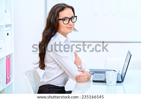 Portrait of young businesswoman working in the office with a laptop.