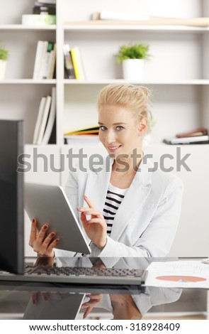 Portrait of young businesswoman working on her presentation at office. Smiling professional woman sitting at desk in front of computer and holding in her hand a digital tablet.  - stock photo