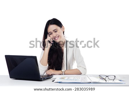 Portrait of young businesswoman working on the table with laptop while talking on the cellphone, isolated on white - stock photo
