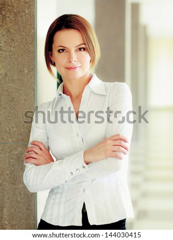 Portrait of young busineswoman standing in office lobby. - stock photo