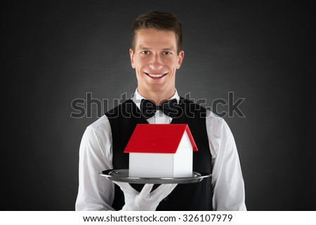 Portrait Of Young Butler Holding Tray With House Model - stock photo