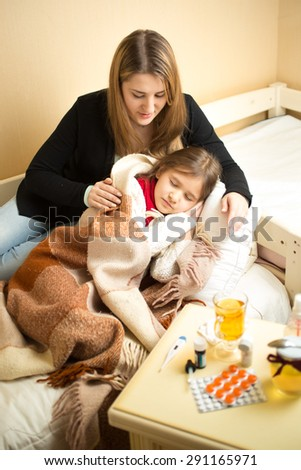Portrait of young caring mother hugging sick girl lying in bed - stock photo