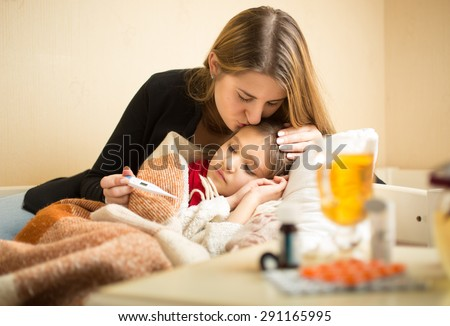 Portrait of young caring mother kissing sick daughter in head - stock photo