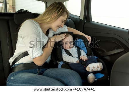 Portrait of young caring mother with her baby boy on car back seat - stock photo