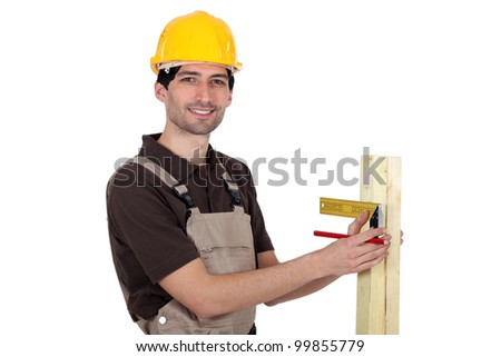 portrait of young carpenter taking measurements - stock photo