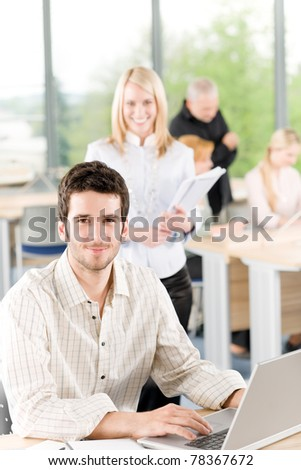 Portrait of young casual business student with team in back - stock photo