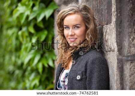 Portrait of young casual woman leaning against stone wall - stock photo