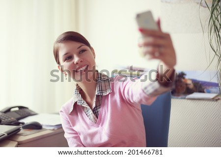 Portrait of young caucasian business woman in pink vest at her office doing selfie on the phone.