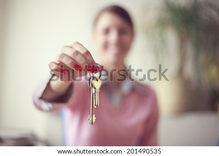 Portrait of young caucasian business woman in pink vest at her office giving the keys. Selective focus - stock photo