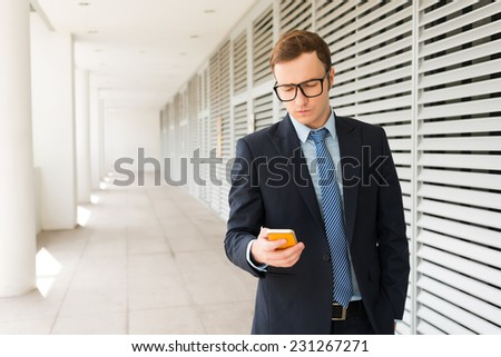 Portrait of young Caucasian businessman texting - stock photo