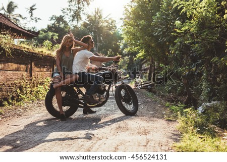 Portrait of young caucasian couple hanging out with motorcycle on village road. Young man and woman on motorbike. - stock photo