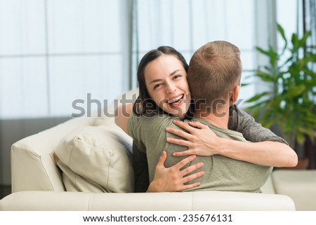portrait of young caucasian couple relaxing on sofa at home, embracing each other and having fun - stock photo