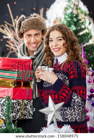 Portrait of young Caucasian couple with disposable cups and Christmas presents standing at store - stock photo