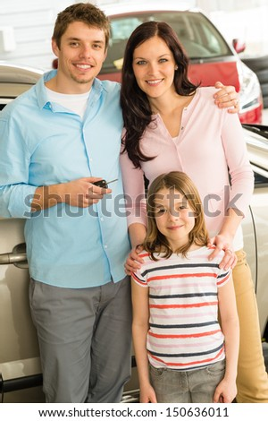 Portrait of young caucasian family with new car - stock photo