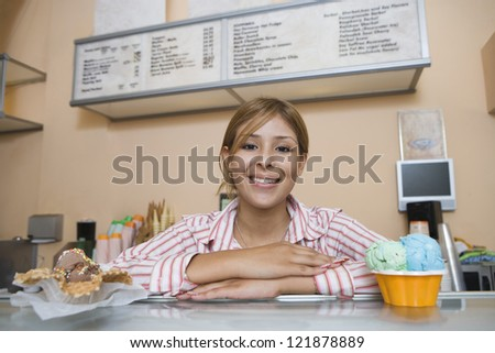 Portrait of young Caucasian female standing by counter with desserts on it - stock photo