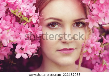 Portrait of young caucasian female surrounded with pink spring flowers