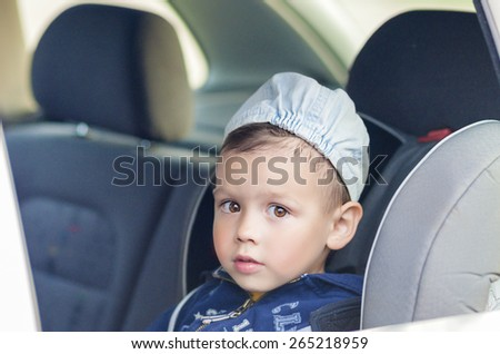 Portrait of Young Caucasian happy Little Boy Sitting on a Car Safety Seat Chair. Horizontal Image - stock photo