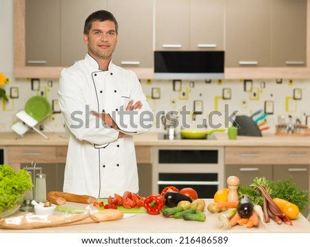 portrait of young caucasian male chef, standing with cut vegetables in front - stock photo