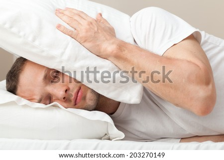Portrait of Young Caucasian man in bed hiding from noise - stock photo