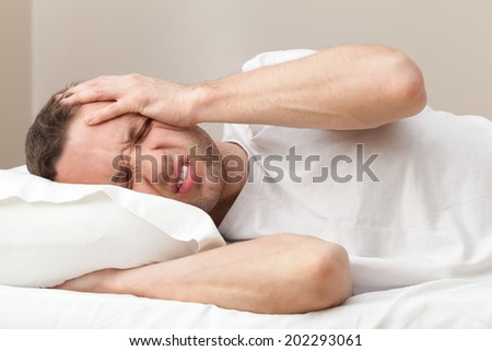 Portrait of Young Caucasian man in bed with headache  - stock photo