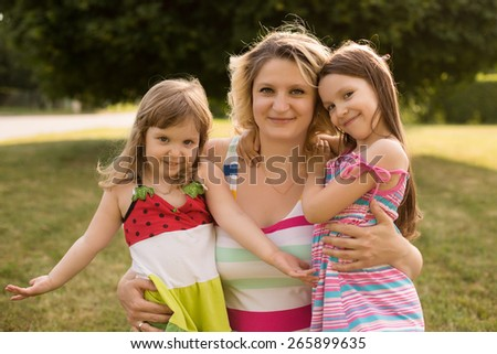 Portrait of young caucasian pregnant woman embracing with her daughters in the meadow of the park. - stock photo
