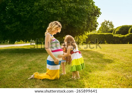 Portrait of young caucasian pregnant woman with her daughters in the meadow of the park. - stock photo